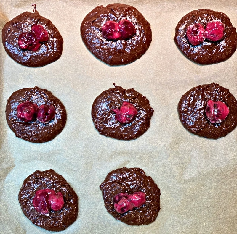 Chocolate Crispy Cookies topped with cherries baked in oven